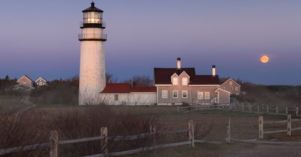 A full moon sets over a foggy field and Highland Light lighthouse in Truro, Cape Cod