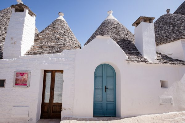A blue arched wood door on a white trulli house in the UNESCO world heritage town of Alberobello, Italy.