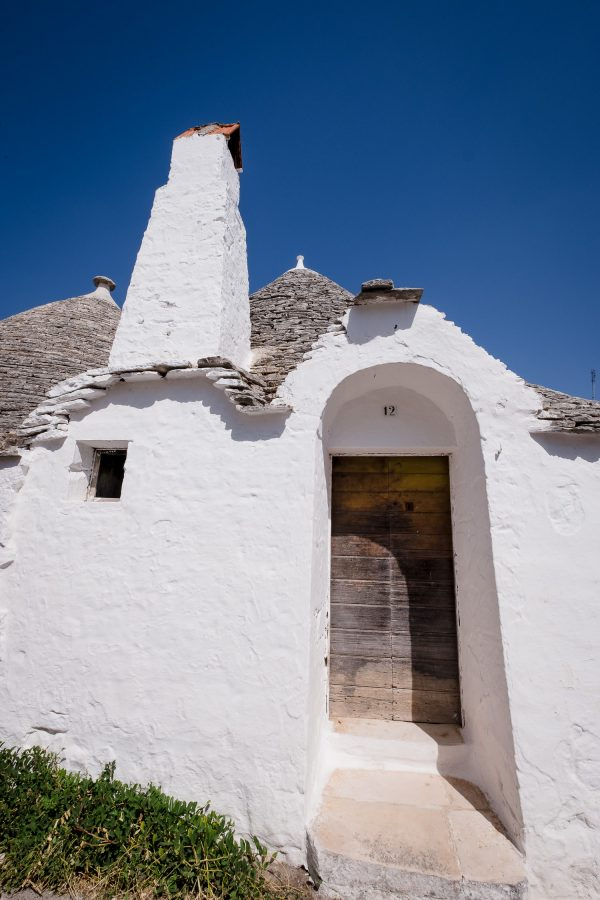 An old wood door on a white-washed Trulli house with chimney in Alberobello, Italy.