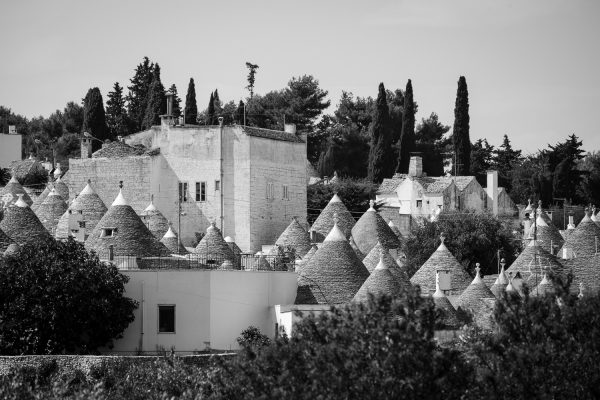 A black and white travel photograph of the skyline of trulli houses in Alberobello, Italy.