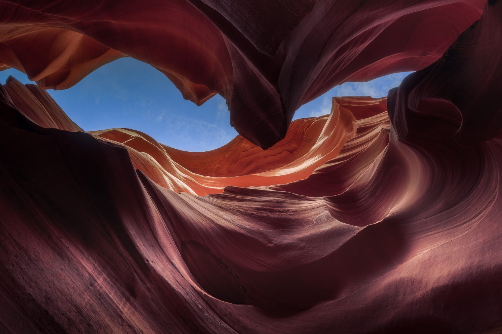 Looking up through the orange sandstone walls of Antelope Canyon at a sliver of blue sky