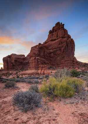 An orange sandstone spire rises from the desert grasses under a sunset sky