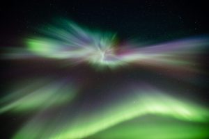 Looking up directly into an aurora borealis corona and the starry sky above.
