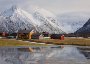 A yellow, blue and red house reflect in a large puddle with snow capped mountains behind them in Austvagoy in the Lofoten Islands of Norway