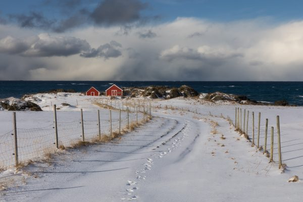 A set of footprints extend through the snow to a red fishing shack as storm clouds roll in from the far off ocean in Austvagoy in the Lofoten Island of Norway