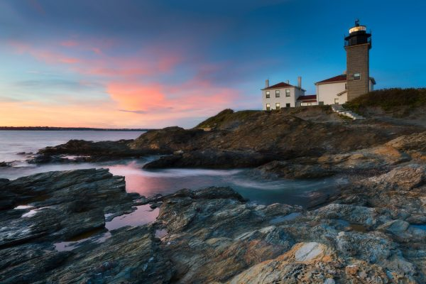 A sunset landscape photo of the ocean, a rocky coastline and beavertail lighthouse in Rhode Island.