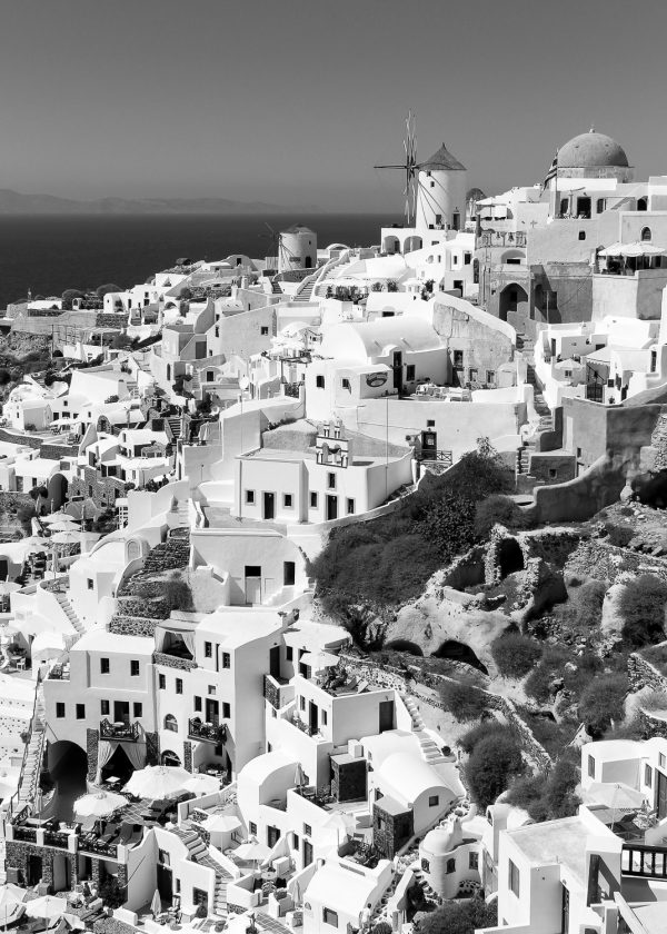 A black and white image of the houses and windmills of Oia Santorini Greece.