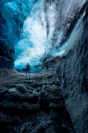 A man walks through a bright blue glacial ice cave in Iceland.