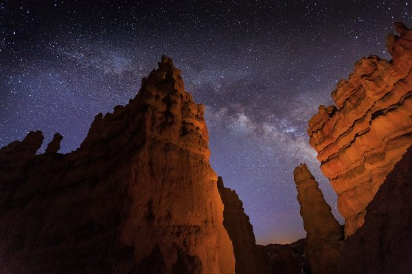 The orange sandstone spires of Bryce Canyon rise up to meet a starry sky and the milky way