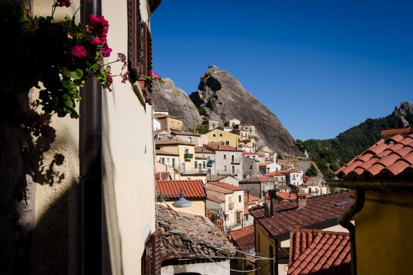 The town of Castelmezzano hangs from a mountain off in the distance with houses and red flowers in the foreground.