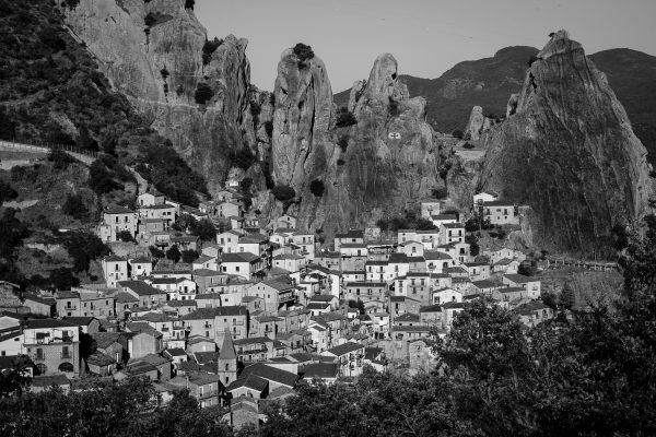 A black and white travel photograph of the town of Castelmezzano in the mini dolomites of Italy.