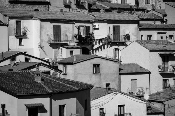 A black and white image of houses and hanging laundry in the town of Castelmezzano, Italy.