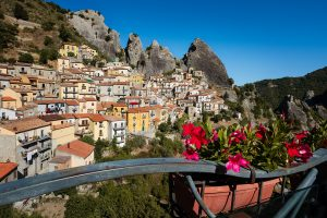 Red flowers in a window box with the town of Castelmezzano, Italy in the background.