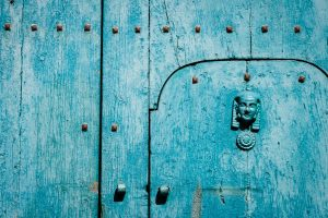 A closeup of an ancient turquoise door with a spine decoration in Castelmezzano Italy.