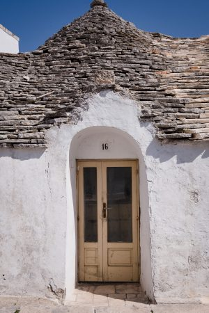 A doors of italy photograph showing an old wood door inside an arched opening on a whitewashed trulli house with cone shaped stone roof in Alberobello, Italy.