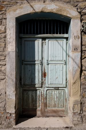 A peeling pale blue wood door on an ancient stone house in Castelmezzano, Italy.
