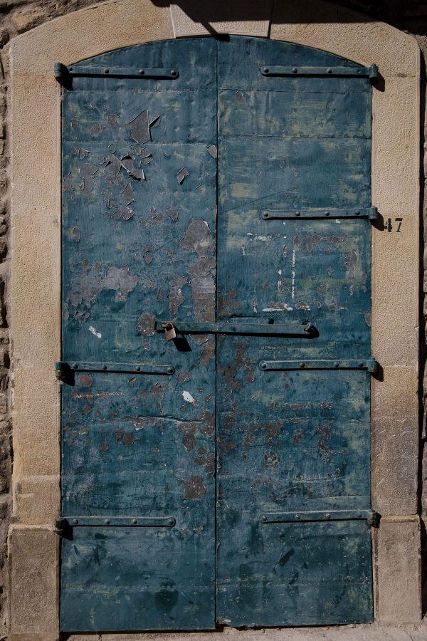 A peeling old blue door in Castelmezzano, Italy.