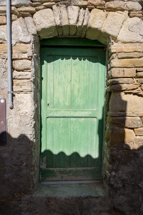 A green wood door on a stone building in Castelmezzano, Italy.