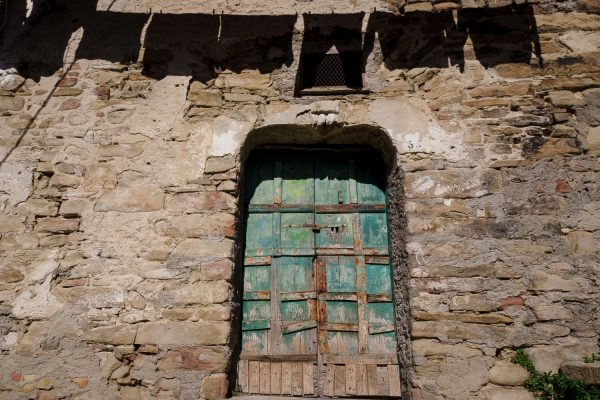 A barricaded green wood door in an ancient stone building with the shadow of hanging laundry above in Castelmezzano, Italy.