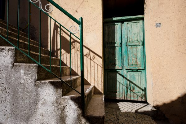 A stairway leads down to a faded green wood door in Castelmezzano, Italy.
