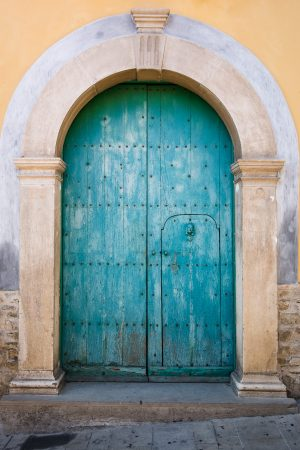 A curved top turquoise wood door on a historic building in Castelmezzano, Italy.