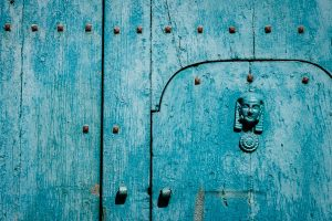 A closeup detail of a spine and rivets on a turquoise wood door in Castelmezzano, Italy.