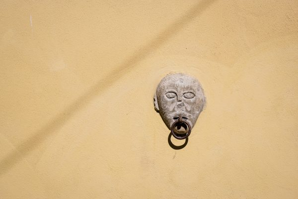 A doorknocker with a face on a yellow door in Castelmezzano, Italy.