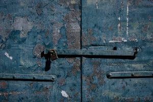 A closeup of a lock on a peeling blue door in Castelmezzano, Italy.