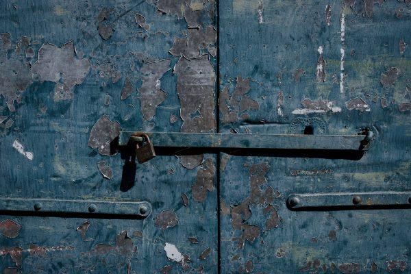 A closeup of a lock on a peeling blue door in Castelmezzano, Italy.