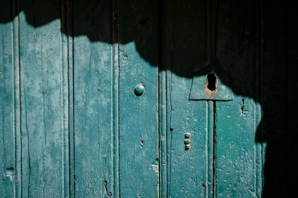 A closeup photo of a antique lock hole on a teal wood door in Castelmezzano, Italy.