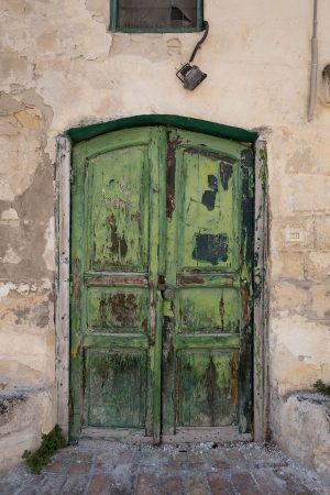 A peeling antique green door in a stone building in the Sassi di Matera, Italy.