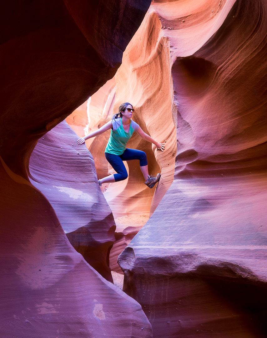 A female landscape photographer wearing a green shirt canyoneering in an orange sandstone slot canyon in Arizona