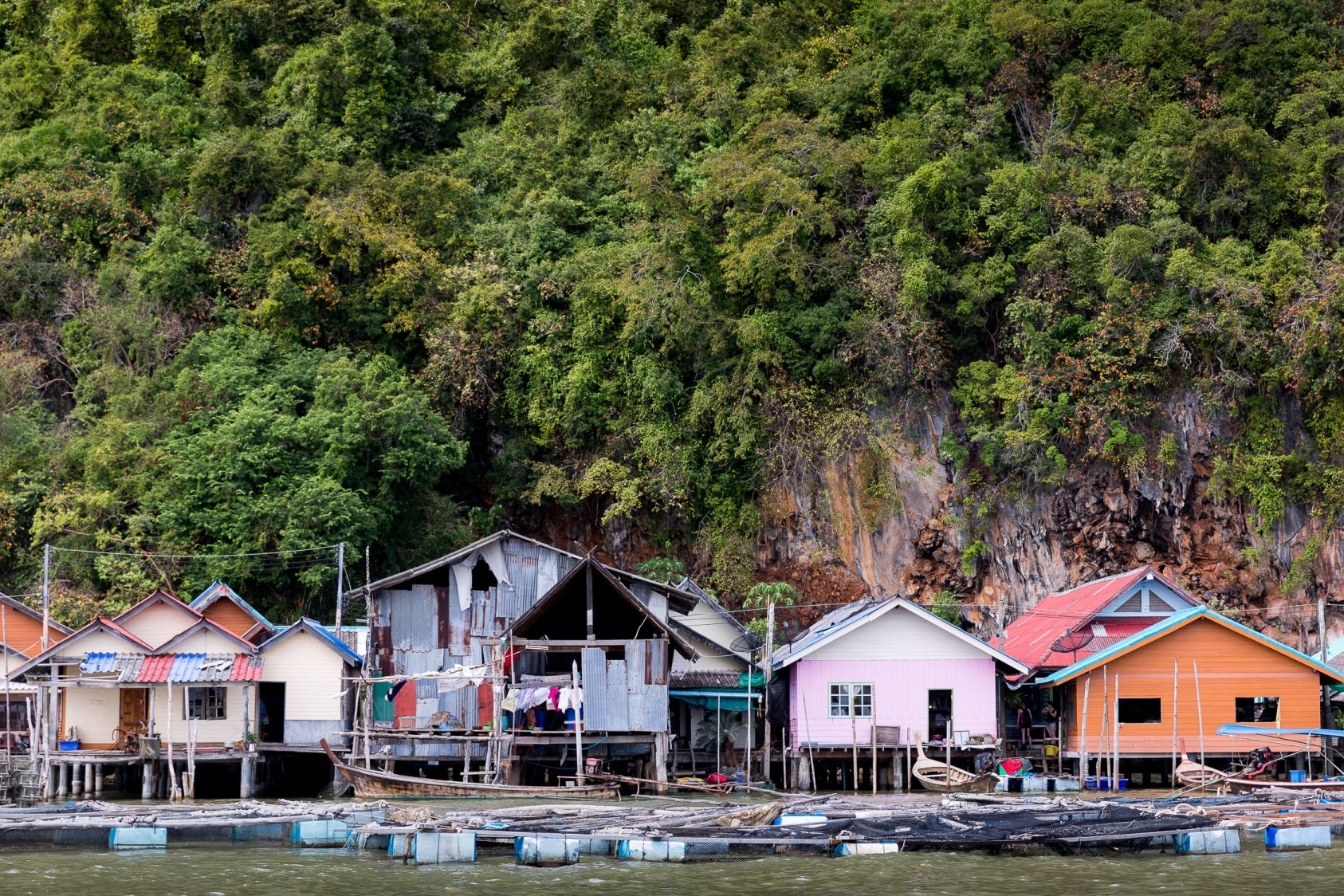 Colorful floating houses below a green jungle in the floating village of koh panyee in Thailand.