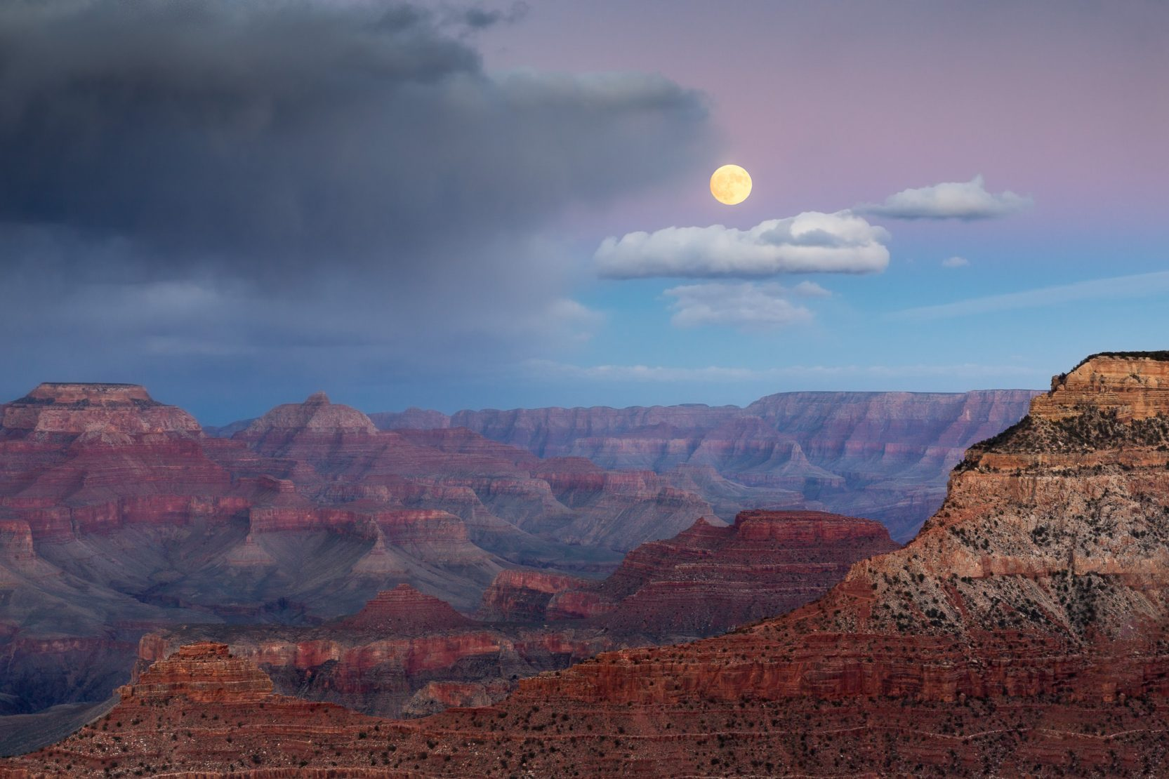 A full moon rises over the grand canyon.