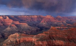 The sandstone walls of the grand canyon glow orange and red just after sunset under a dust storm purple sky.