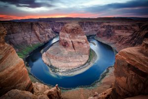 A u shaped bed in a river with tall canyon walls surrounding it at Horseshoe bend in Page, Arizona