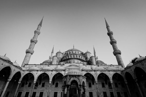 A black and white travel photo of the blue mosque as seen from the inner courtyard in Istanbul, Turkey