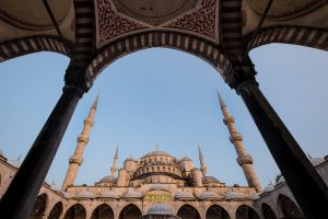 The minarets and archways of the blue mosque are seen through the frame of another archway in Istanbul, Turkey