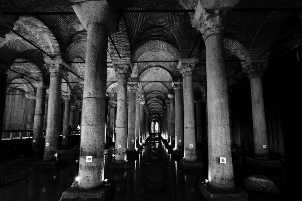 A travel photograph in black and white from the inside of the Basilica Cistern in Istanbul, Turkey showing a row of columns, coved ceilings and water below.