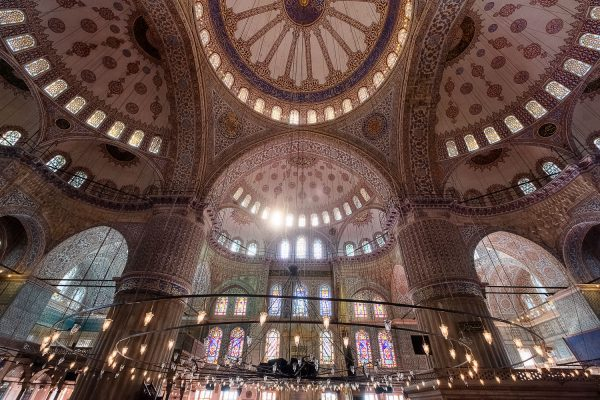 A travel photograph by Kathryn Wallace Yeaton showing the many stained glass windows and mosaic tiles inside of the Blue Mosque in Istanbul, Turkey