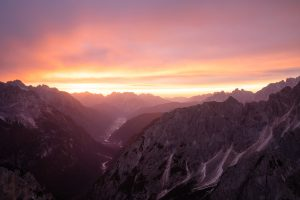 pink clouds at sunrise over mountains in italian dolomites