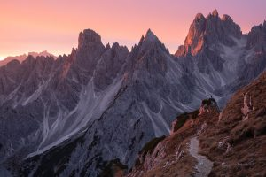 man stands in front of mountain at sunrise