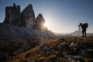 sun star behind mountain with photographer in foreground