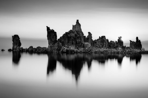 A black and white landscape photograph of a sunstar and a tufa formation reflecting in Mono lake California