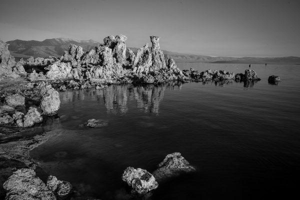 A black and white landscape photograph of tufa formations in Mono Lake California