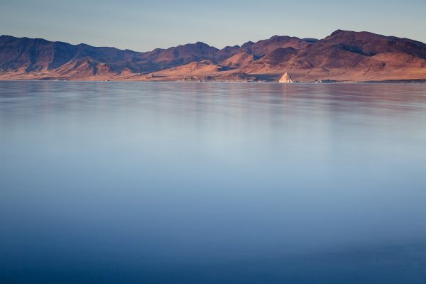 A landscape photograph of the glassy blue surface of Pyramid Lake in Nevada, with a sunlit pyramid rock formation and orange mountains on the opposite side of the lake.