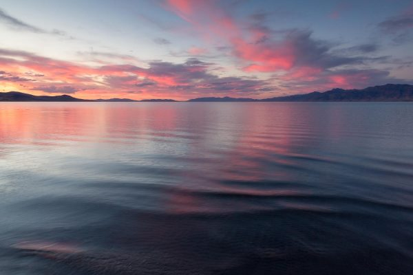 A landscape photograph of small ripples on the surface of Pyramid Lake in Nevada and reflect the orange and pink sunset clouds above