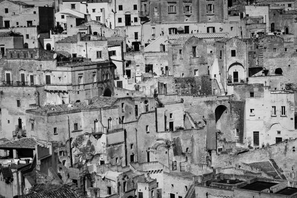 A black and white image of the many layers of buildings on top of each other in the historic Sassi di Matera in Italy.