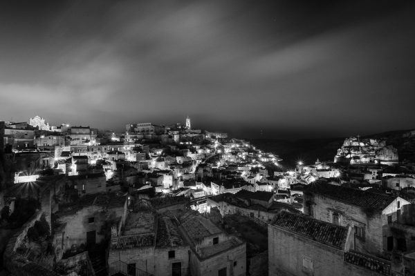A black and white long exposure night photograph of the Sassi di Matera in Italy.