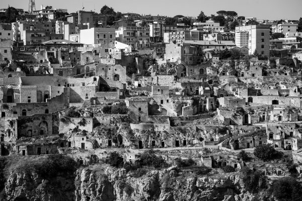 A black and white photograph of the many layers of the Sassi di Matera cave dwellings in Italy.